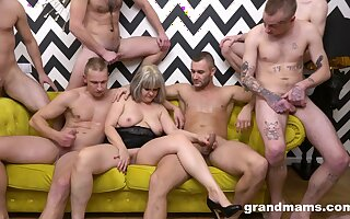 Naked mature is surrounded by younger lads waiting not far from fuck their way hard