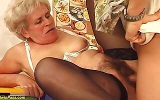 Hairy Hungarian granny is sucking a much younger guys dick together with getting fucked hard, in return